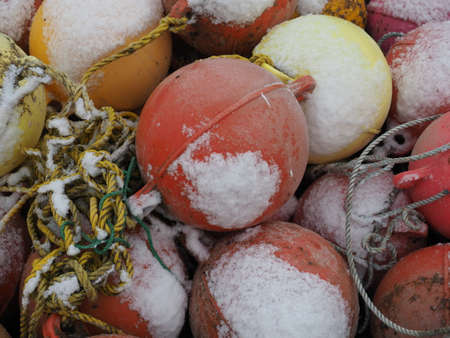 Colourful buoys and beacons covered with snow on ocean seaside in winter