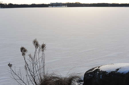 Frozen lake covered with white snow during dusk and sunset in Sweden in winter Stok Fotoğraf