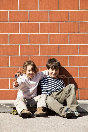 two children, brother and sister sitting against a wall Stock Photo - 13234788