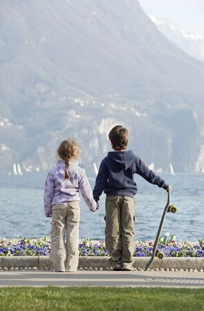 two children, brother and sister holding hands looking at the lake photo