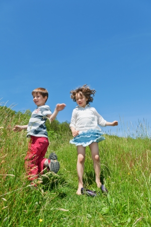 meadowland: two children playing together in the grass