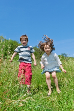 two children playing together in the grass photo