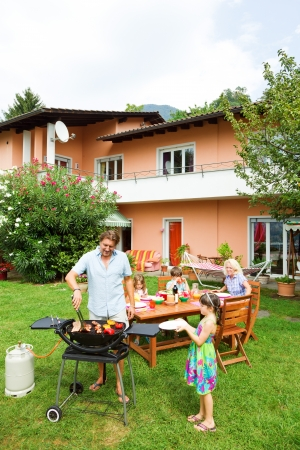 bbq picnic: Family having a barbecue in the garden, eating Stock Photo