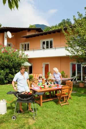 fiesta familiar: Familia que tiene una barbacoa en el jard�n, comer
