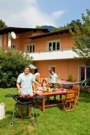 family garden: Family having a barbecue in the garden, eating Stock Photo