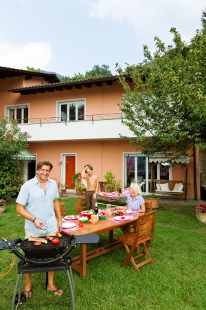barbecue party: Family having a barbecue in the garden, eating Stock Photo