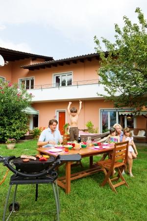 家庭在花园里有烧烤,吃