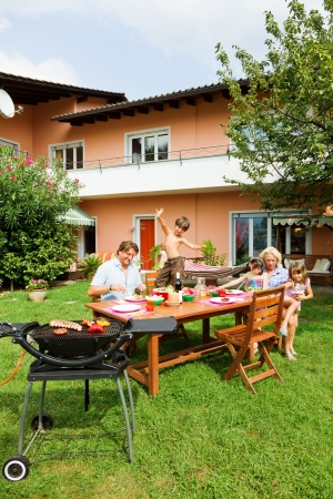 garden barbecue: Family having a barbecue in the garden, eating Stock Photo