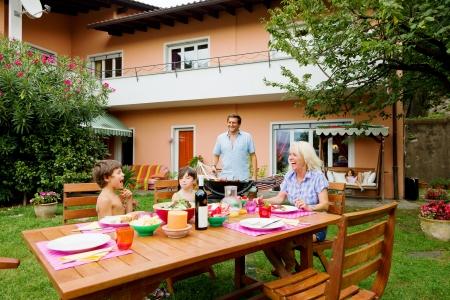 famiglia in giardino: Famiglia avendo un barbecue in giardino, mangiare Archivio Fotografico