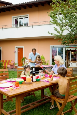 Family having a barbecue in the garden, eating photo