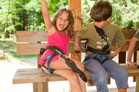 little girl sitting: brother and sister in a park adventure