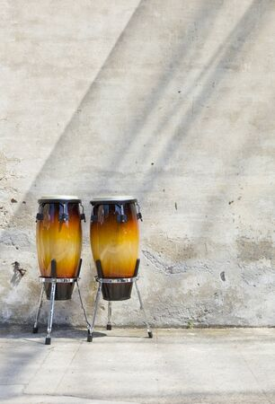 bongos: two congas in front of a wall
