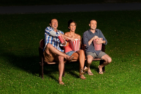 lifestyle outdoors: three friends in exterior cinema