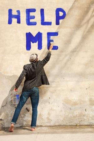 persona escribiendo: hombre escribe en una pared que me ayude