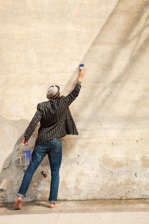 man painting: man from behind, writes on a wall