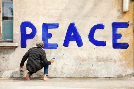 remonstrance: man writes on a wall peace