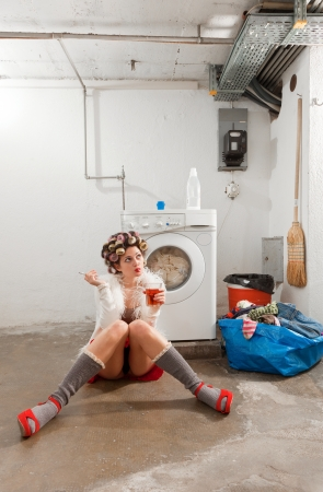 launderette: young woman in laundry, she drink Stock Photo