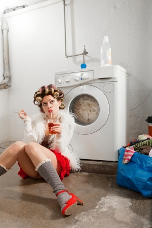 young woman in laundry, she drink Stock Photo