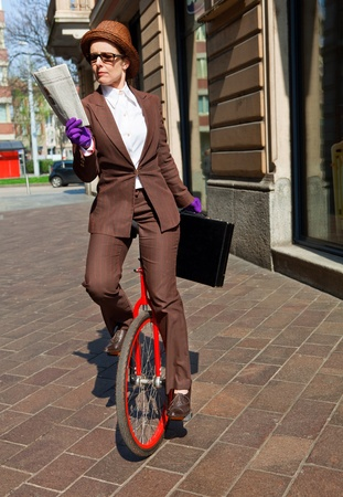 woman through the city with the unicycle to go to work photo