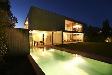 exteriores: casa de la belleza en la noche con piscina