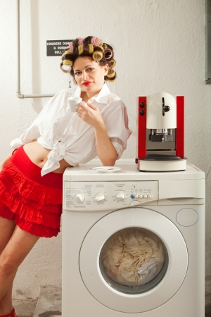 lavage: young woman in laundry, she drink coffee