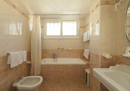 hotel bathroom: bathroom with beige tiles and decorations