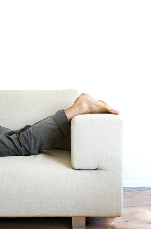 Detail of the feet of man lying on the sofa photo