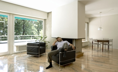Interior of modern house, living room with a tired man resting Stock Photo