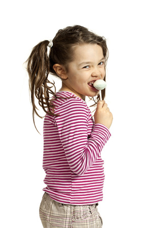 girl licking: Close-up of little girl with a lollipop, isolated on white background
