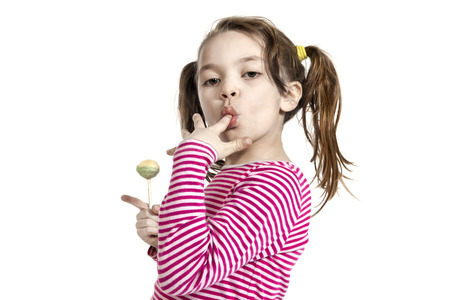 Close-up of adorable little girl with a lollipop, isolated on white background photo
