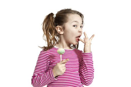 licking finger: Close-up of adorable little girl with a lollipop, isolated on white background