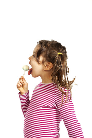 portrait of little girl with a lollipop, isolated on white background photo