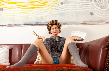 underpants: sexy girl eating spaghetti on the couch Stock Photo