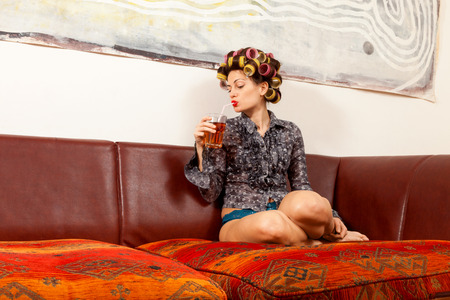 sexy girl with drink on the couch in the living room photo