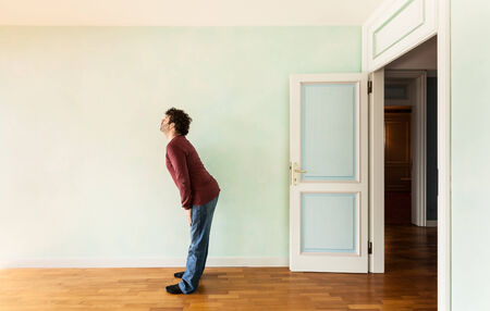portrait of a weird guy in a room with the door open Stock Photo