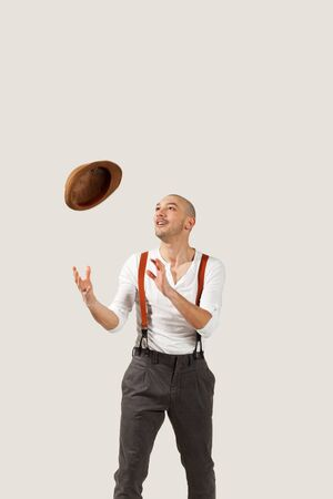 man throws his hat in air, portrait in studio  Stock Photo