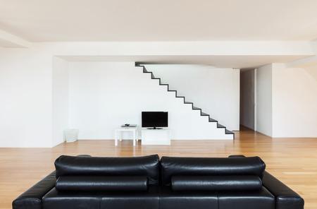 divan: Interior, precioso loft, piso de madera, sof� negro Foto de archivo