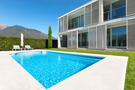 the window: Modern villa with pool, view from the garden Stock Photo
