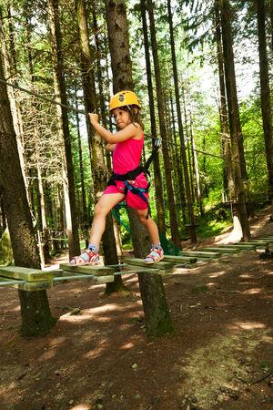 niño escalando: retrato de un niño en un parque de cuerdas