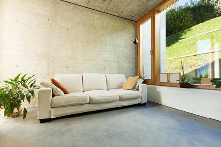 belle maison moderne dans le ciment, les intérieurs, avec divan