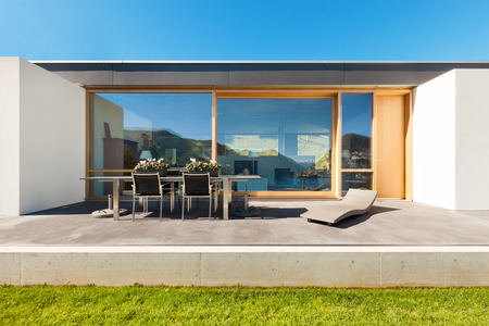 garden furniture: beautiful modern house in cement, view from the garden