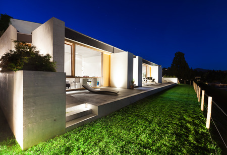 beautiful modern house in cement, view from the garden, night scene Stock fotó