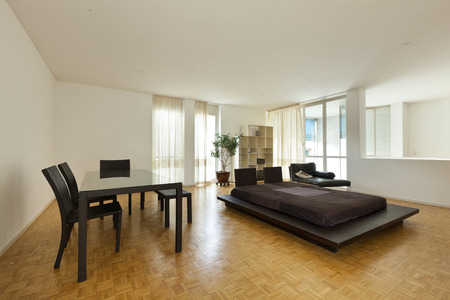 Bright duplex with hardwood floors, large room with double bed and table photo