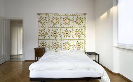 interior white bedroom, decorative carpet on the wall photo