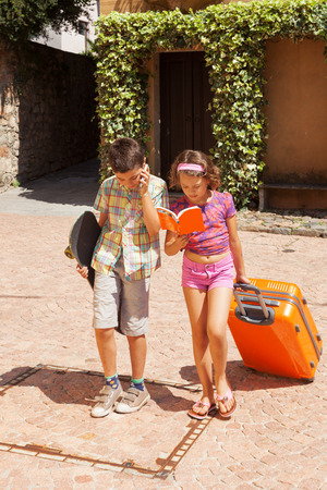 comunication: Young couple with suitcase in exterior. Romantic scene Stock Photo
