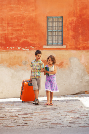 Young couple with suitcase in exterior. Romantic scene photo