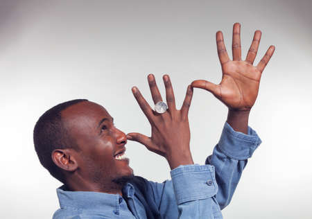derision: Young African boy with mocking gesture with two hands Stock Photo
