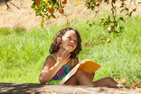 studing: a beautiful little girl reading a yellow book in the garden with a colorated dress next to the tree
