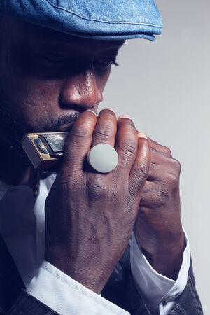 harmonica: musician plays the harmonica on white background