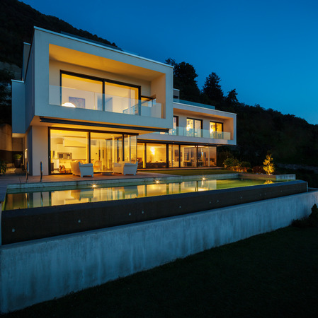 illuminated: Modern house with pool and garden, summer time